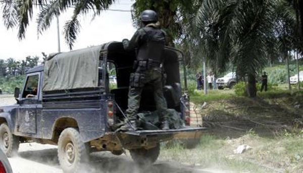 The bodies of Malaysian police commandos killed in the firefight on Friday are loaded into a truck.