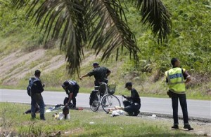 Malaysian police search suspects leaving the security cordon in Sabah.