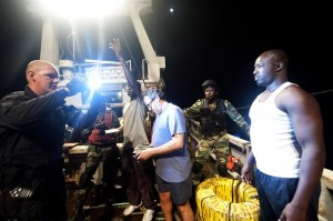 (July 17, 2011) - Petty Officer 2nd Class James Haurand (LEFT) takes an identification photo of a crewmember aboard a Senegalese fishing vessel as part of an African Maritime Law Enforcement Partnership (AMLEP) boarding mission with Coast Guard and Senegalese boarding teams. (U.S. Coast Guard photo by Petty Officer 2nd Class Etta Smith/RELEASED)