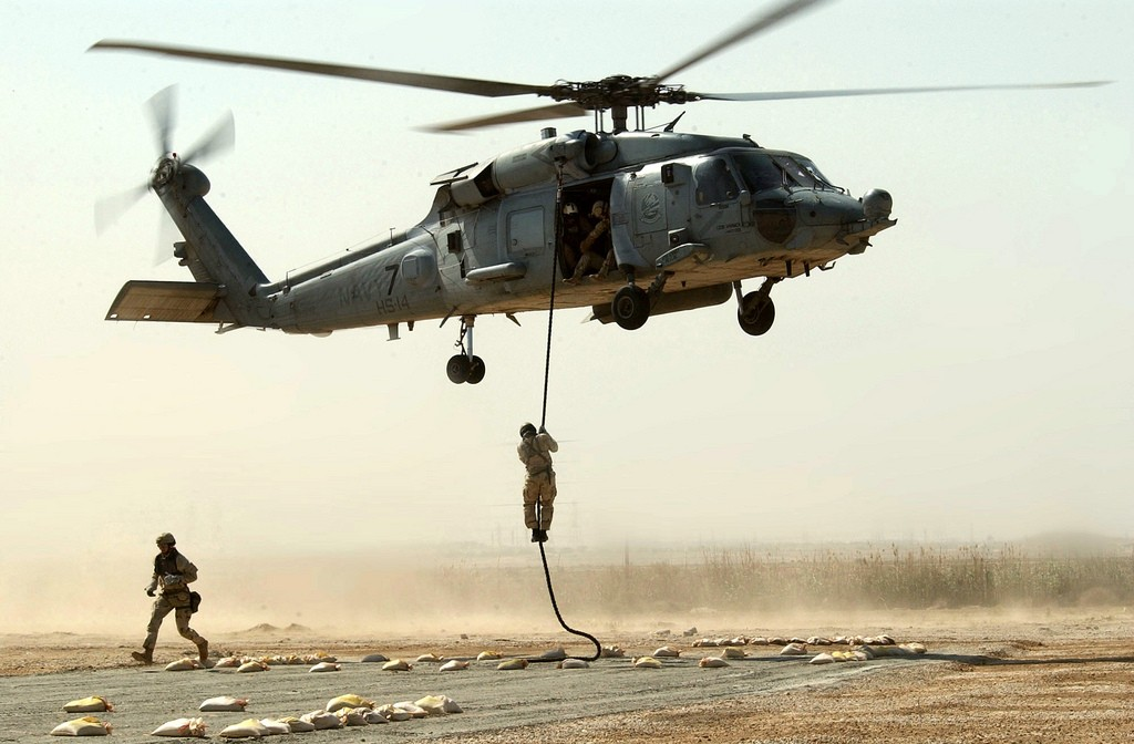 Members of a Naval Special Warfare team conduct a fast rope insertion training operation from an SH-60 Seahawk helicopter