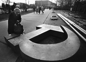A woman reaches into her bag, which rests on a fallen Soviet hammer-and-sickle on a Moscow street in 1991, Getty Images
