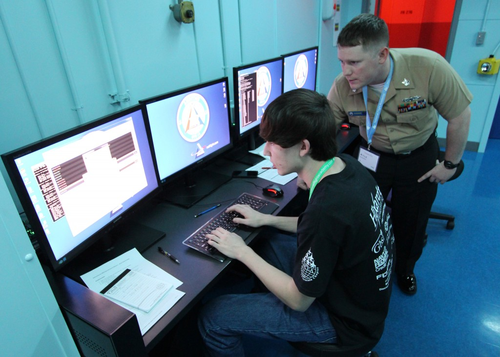 150125-N-PK678-032 PENSACOLA, Fla. (Jan. 25, 2014) Information Systems Technician 1st Class Kyle Gosser, an instructor at the Center for Information Dominance Unit Corry Station, mentors a local high school student participating in the inaugural Cyberthon competition at the National Flight Academy at Naval Air Station Pensacola during the weekend of Jan. 23-25. The Cyberthon competition tests student teams on their abilities to use the computer skills they learned in their classrooms to defend and defeat cyber attacks on websites. (U.S. Navy photo by Ed Barker/Released)