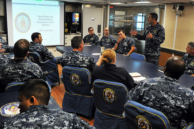 Capt. Frank Olmo, deputy commander, Naval Surface and Mine Warfighting Development Center (SMWDC), introduces SMWDC and the new career opportunities it provides junior surface warfare officers (SWOs) during a brief aboard USS Bunker Hill (DDG 52). U.S. Navy photo).