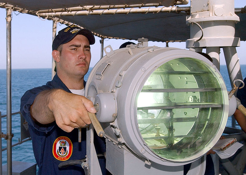 800px-US_Navy_020623-N-5329L-007_Signalman_2nd_Class_Eric_Palmer_signals_the_U.S._Navy_mine_hunter_coastal_ship_USS_Raven_%28MHC_61