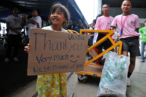 111023-N-WW409-696 UTAPAO, Thailand (Oct. 23, 2011) A child from the local community holds a sign thanking the U.S. Sailors from the guided missile destroyer USS Mustin (DDG 89) and members from the Royal Thai Armed Forces during a community service event organized by the Princess Pa Foundation, Thai Red Cross Society. More than 40 Sailors from Mustin volunteered their time with the local community and members from the Royal Thai Armed Forces with assisting in preparing more than 5,000 packages. (U.S. Navy photo by Mass Communication Specialist 1st Class Jennifer A. Villalovos/Released)