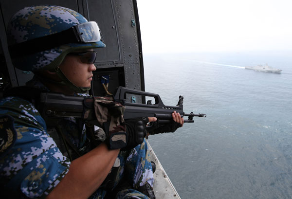 A Chinese Navy soldier observes from a helicopter during an escort mission in the Gulf of Aden, Aug 26, 2014. This is the 18th convoy fleet sent by the Chinese People's Liberation Army Navy for these missions since 2008. [Photo/ Xinhua]