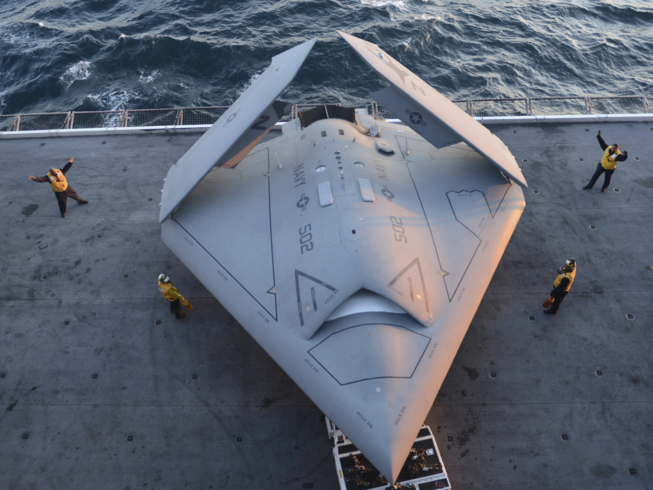 This image provided by the US navy shows sailors moving an X-47B Unmanned Combat Air System (UCAS) demonstrator onto an aircraft elevator aboard the aircraft carrier USS George H.W. Bush Tuesday, May 14, 2013. The drone was launched off the George H.W. Bush to be the first aircraft carrier to catapult launch an unmanned aircraft from its flight deck. (AP Phioto/U.S. Navy photo by Mass Communication Specialist 2nd Class Timothy Walter)