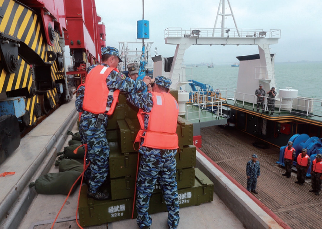 "Sansha Maritime Militia participate in exercises to load materials on their vessels. 32-kg crates labeled ""light weapons"" are shown being loaded with cranes. The exercises were also featured on the Guangzhou Military Region Website in September 2015. Image source: National Defense"