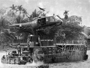 An armored troop carrier modified with a landing platform prepares to receive a UH-1 MEDEVAC helicopter. (Mobile Riverine Force Association)