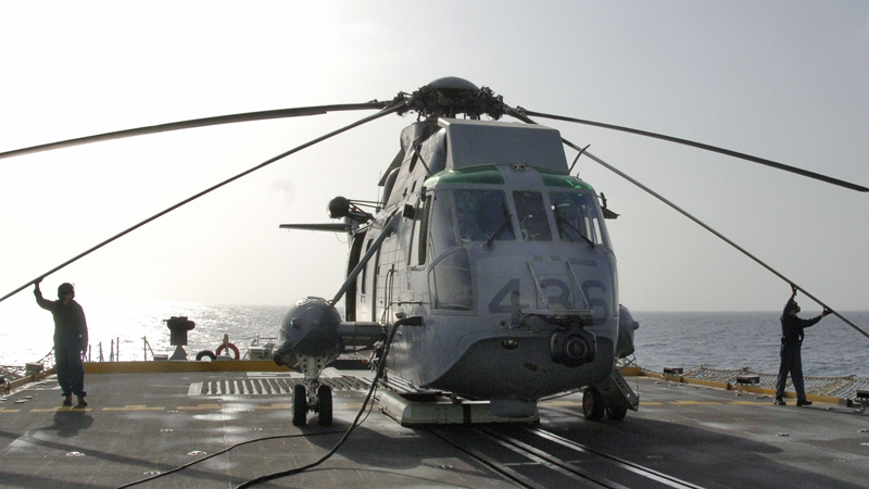 "IS2005-2137a 31 July, 2005 Persian Gulf (Arabian Gulf) region Crewmembers from HMCS Winnipeg's helicopter detachment prepare a CH-124 Sea King for flight operations in the Gulf of Oman. The Canadian frigate is part of Operation ALTAIR, Canada's maritime contibution to the U.S.-led coalition campaign against terrorism mission known as Operation ENDURING FREEDOM. Photo: Sgt Frank Hudec, Canadian Forces Combat Camera Le 31 juillet 2005 Région Arabo-Persique Des membres de l'équipage du détachement d'hélicoptères du NCSM Winnipeg préparent un hélicoptère dans le but de participer à des opérations aériennes dans le golfe d'Oman. La frégate canadienne participe à l'opération Altair, la contribution maritime du Canada à la campagne dirigée par les É. U., menée par la coalition contre le terrorisme et connue sous le nom d'opération Enduring Freedom. Photo : Sgt Frank Hudec, Caméra de combat des Forces canadiennes. Image size = 9.86"" x 5.34"" 300 DPI 2960 x 1604 pixels"