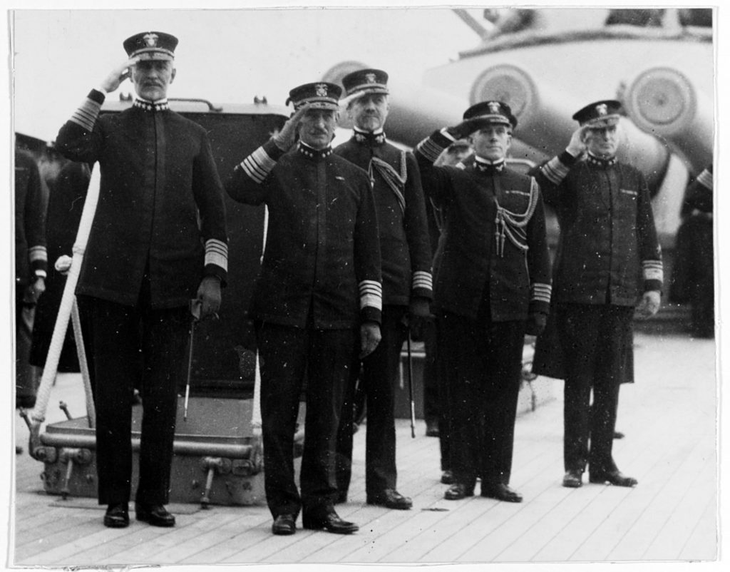 (Previously Unpublished) Commander, U.S. Naval Forces in Europe, Admiral William S. Sims, salutes with the Commander, Atlantic Fleet, Admiral Henry T. Mayo, with their chiefs of staffs on board the flagship of the Atlantic Fleet, USS Pennsylvania (BB-38). After the armistice in November of 1918, Sims and Mayo assumed four star rank. Their close collaboration during the First World War provided the template for headquarters ashore to support future U.S. Navy operations at sea. Together, the staffs serving under Sims and Mayo pioneered contemporary concepts of joint and combined naval command.