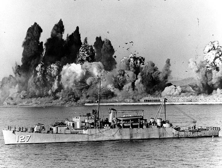 During the Evacuation of Hungnam, 24 December 1950, USS Begor (APD-127) stands offshore, ready to embark the last UN landing craft, as demolition charges wreck Hungnam's port facilities. (U.S. National Archives)