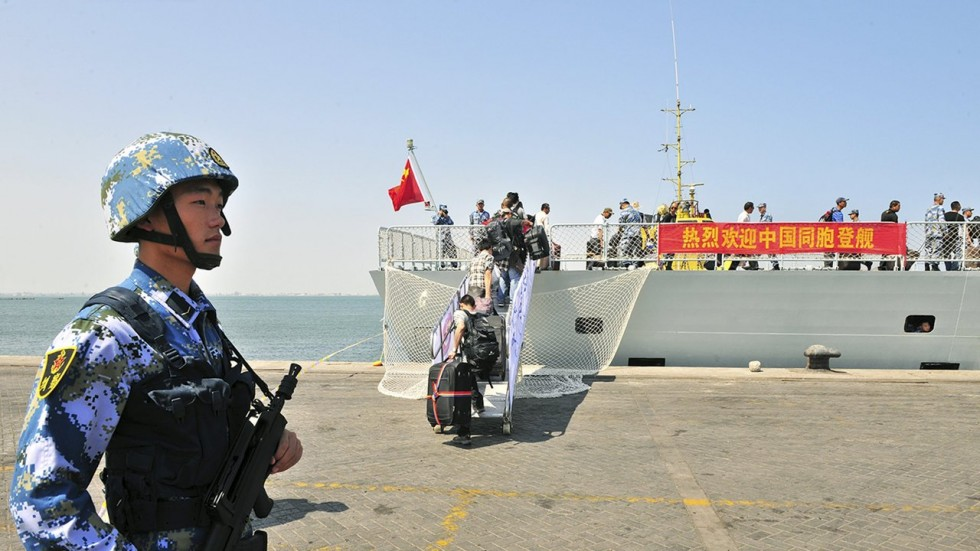 A People's Liberation Army Navy soldier stands guard as Chinese citizens board a Chinese naval ship at a port in Aden last year. Photo: Reuters