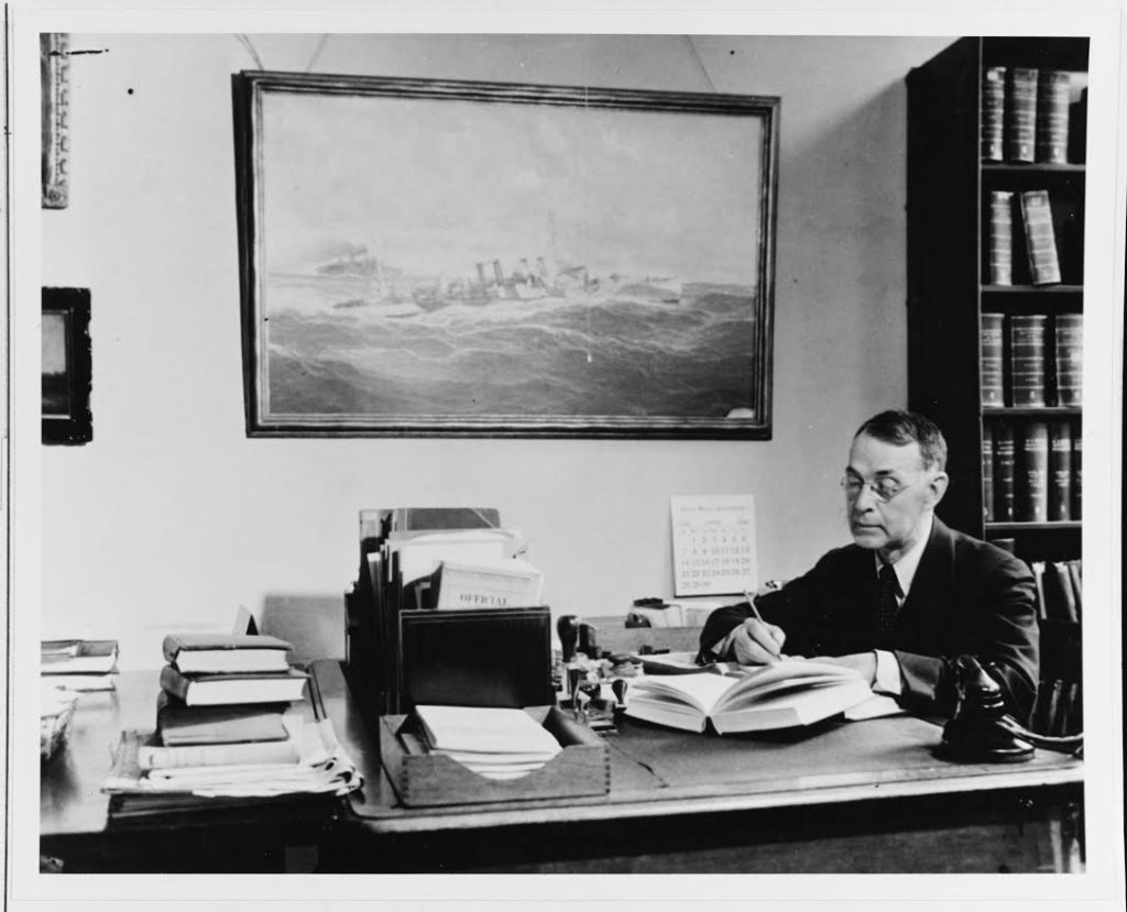 (Previously Unpublished) Dudley W. Knox requested transfer to the retired list of the U.S. Navy, seeking to broaden U.S. Navy efforts to engage the American public in understanding the influence of sea power upon history. During the 1920s and 1930s, Knox helped organize historical research and preservation efforts within the Navy Department. In this role, he also remained heavily involved with the Office of Naval Intelligence. Fusing historical research with efforts to meet contemporary challenges, Knox served as a trusted personal adviser to President Franklin. D. Roosevelt. The painting behind him is that of a destroyer escorting a convoy during the First World War. During the war, Knox was heavily involved in convoy operations.