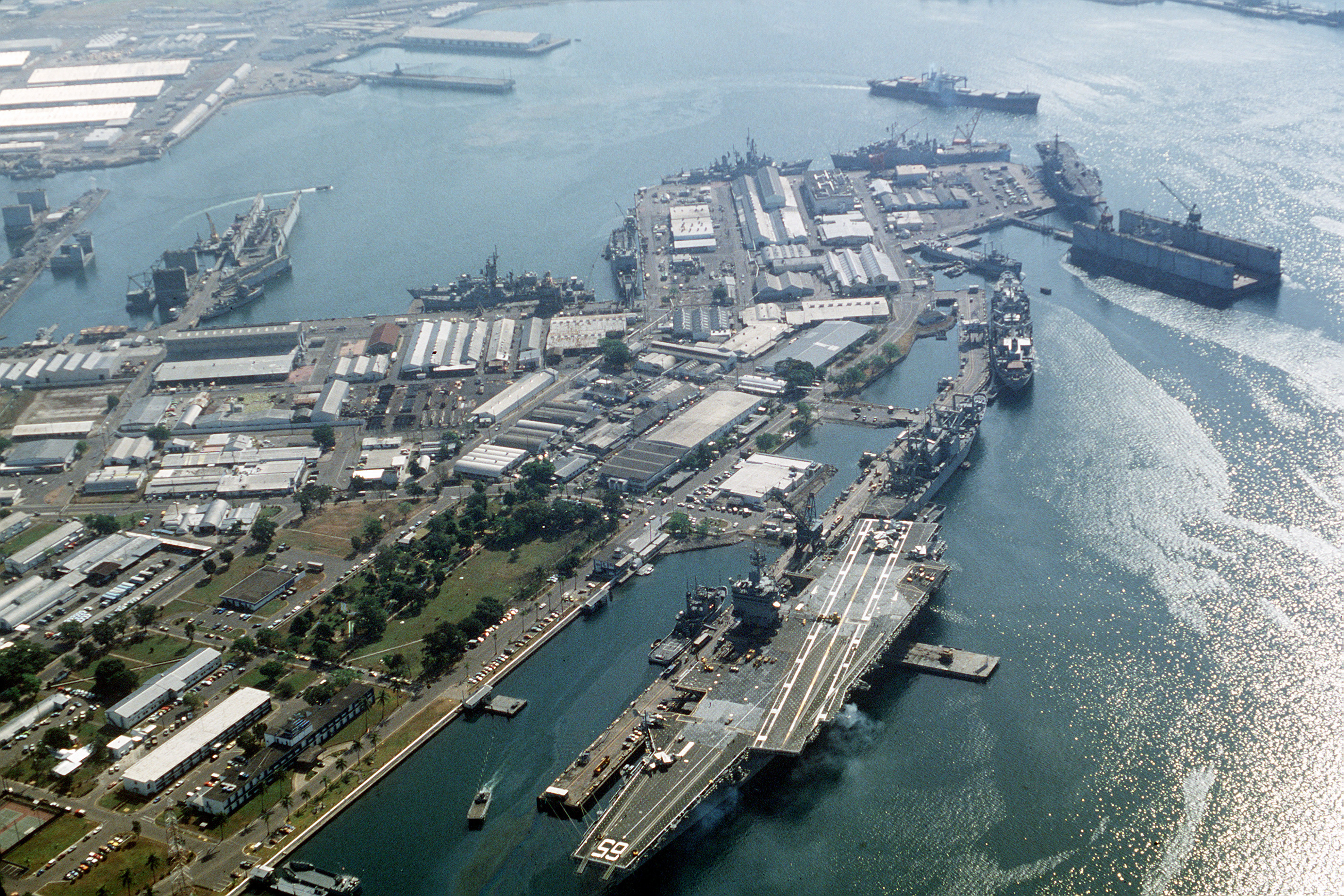 An aerial view of ships moored at the station. The nuclear-powered aircraft carrier USS ENTERPRISE (CVN-65) is in the foreground. (Vern Rowe)